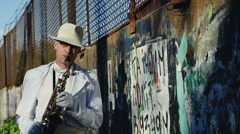 Saxophonist against a wall with graffiti and power lines. Series. Stock Footage