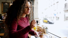 Portrait of pretty young woman eating cup cake in cafe, slow motion - stock footage