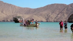 People come out of the boat to the shore of Musandam peninsula, Oman Stock Footage