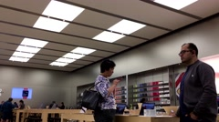 One side of people making phone call inside Apple store Stock Footage
