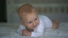 Cute baby laughing lying on the bed Stock Footage