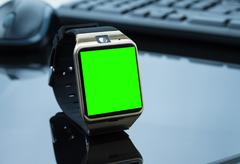 smartwatch near computer pc keyboard and mouse with chroma key green screen - stock photo