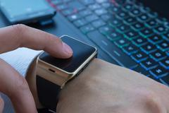 Business man using smartwatch app near pc keyboard and smartphone Stock Photos