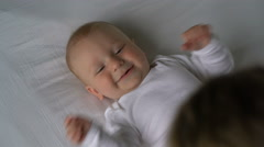 Mother tickles the baby and he laughs lying on the bed Stock Footage