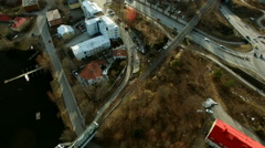 Aerial shot of a railbus nearing a bridge over a street in Savonlinna, Finland Stock Footage