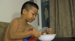Little Thai boy eating instant noodles 4k UHD (3840x2160) Stock Footage