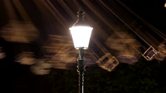 Night Lamp and Blurred Carousel in the Amusement Park. Stock Footage
