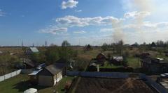 Burning grass near village - stock footage