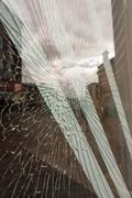 Cracked Glass window with safety tape. Impact area shows many cracks. Defocus Stock Photos