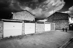 Two twins walk near garages as pending storm clouds mass over their heads. Mo Stock Photos