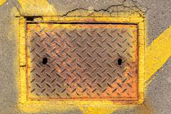 Rusty metal man hole access panel cover surrounded by tarmac and yellow paint - stock photo