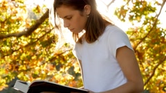 Beautiful young female academic student reading a book studying fall autumn park Stock Footage