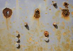 Several areas of rust and rusting bolts on a grey metal surface background. Stock Photos