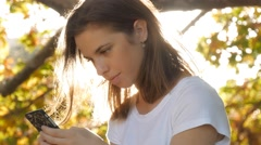 Happy young girl is texting boyfriend on mobile smart phone in autumn fall park - stock footage