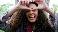 Portrait of happy young woman making love heart gesture with hands, slow motion Stock Footage