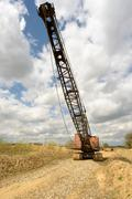 Large and aged industrial crane used for excavation and soil extraction - stock photo
