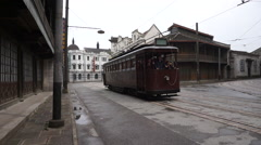 Old styled tram car driving on street Stock Footage