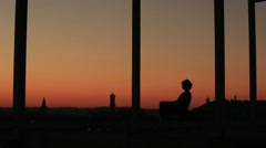 Silhouette of a beautiful girl meditating in the sunset at the city background Stock Footage