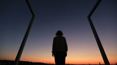 Silhouette of young woman raising up hands to the sky on sunset. Modern high Stock Footage