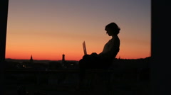 Silhouette of young businees woman using her laptop on the sunset background in Stock Footage