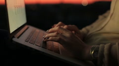 Close up of woman's hands typing on the laptop's keyboard on sunset. Young Stock Footage