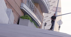 Young man skateboarding down steep city hill 4K Stock Footage