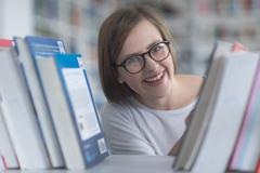 Portrait of famale student selecting book to read in library Stock Photos