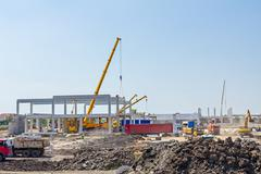 Mobile crane is carry concrete joist to assembly huge hall. Landscape transfo Stock Photos