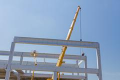 Height worker is high up on concrete frame without proper safety equipment. - stock photo