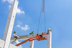 Mobile crane is carry concrete joist to assembly huge hall. - stock photo