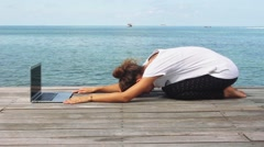 Yoga woman training on the wooden floor with laptop Arkistovideo