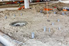 Placing set of new plastic sewer pipes into the ground. Stock Photos