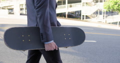 Slow motion business man walking with skateboard 4K 4K Stock Footage