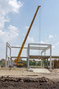 Mobile crane is carry concrete joist to assembly huge hall. Landscape transfo - stock photo