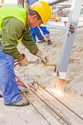 Metal gas cutting with acetylene torch, sparks flies to the ground - stock photo