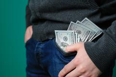Man putting a one hundred dollar banknotes into the chest pocket Stock Photos