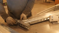 A worker putting togther metal struts in factory Stock Footage