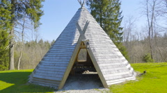 A wooden teepee in the middle of the grass Stock Footage
