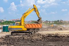 Excavator is working on construction site. Caterpillar in action. - stock photo