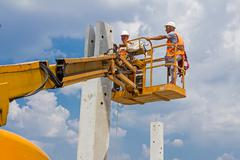 Rigger is in the cherry picker on construction site - stock photo