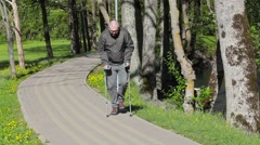 Disabled man with crutches walking on path in the park Stock Footage