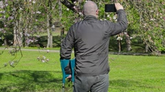 Disabled man with crutches filmed as  blossoming apple tree Stock Footage