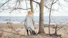 Girl in coat walking and standing by the tree on the beach Stock Footage