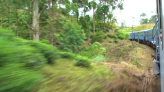 Train winding it's way through The Highlands & tea estates, Sri Lanka Stock Footage