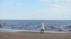 Girl in the coat walks on the sandy beach Stock Footage