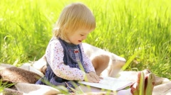 Portrait of cute little girl sitting on picnic blanket holding big book in hands Stock Footage