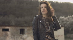 Girl in dress and leather jacket walking on the parapet in front of an abandoned Stock Footage