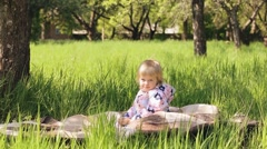 Funny child sitting on picnic blanket in sunny garden or backyard on spring day. Stock Footage