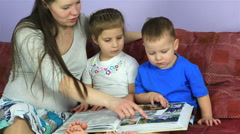 Mom with kids consider an album with photos. Happy family waiting for third Stock Footage