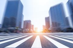 Traffic on road intersection near modern office buildings at sunrise Stock Photos